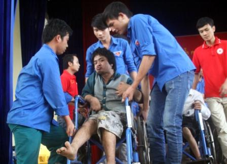 Các tình nguyện viên giúp người khuyết tật, nạn nhân chất độc da cam nhận xe lăn từ các nhà hảo tâm (ảnh: AT)