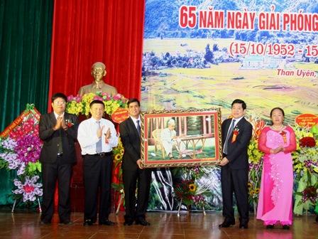 Đồng chí Nguyễn Khắc Chử - Bí thư Tỉnh ủy tặng bức ảnh Bác Hồ ngồi làm việc cho huyện Than Uyên