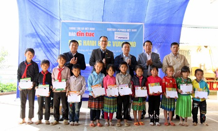 Đại diện lãnh đạo Báo Tin tức, Cơ quan thường trú Thông tấn xã Việt Nam tại Lai Châu, UBND huyện, Phòng Giáo dục huyện Tân Uyên tặng quà cho học sinh