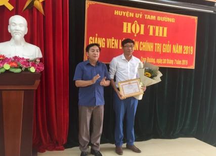 Đồng chí Sùng Lử Páo-Phó BT Thường trực Huyện ủy, Trưởng BTC Hội thi trao giải thưởng cho giảng viên đạt giải Nhất