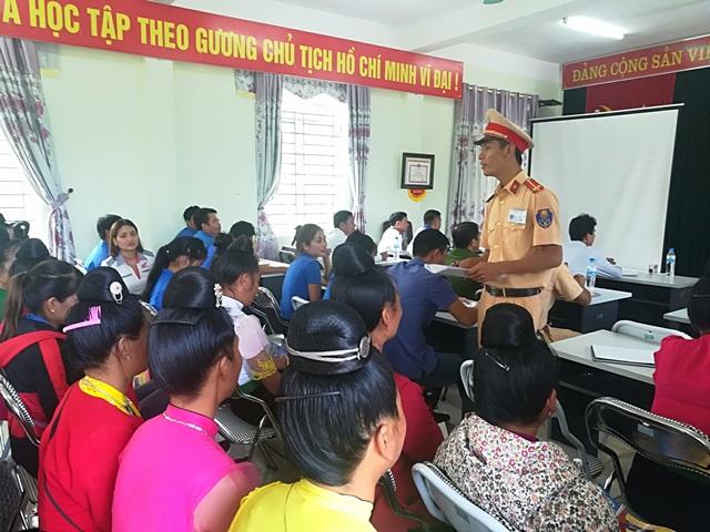Cán bộ đội CSGT Công an huyện Than Uyên tuyên truyền luật giao thông tại hội nghị